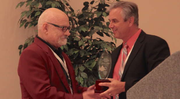 Ken Archer, new SPS president (right), presents the Lifetime Achievement Award to Frank Macchia, Vanguard University professor and 'Pneuma' editor.