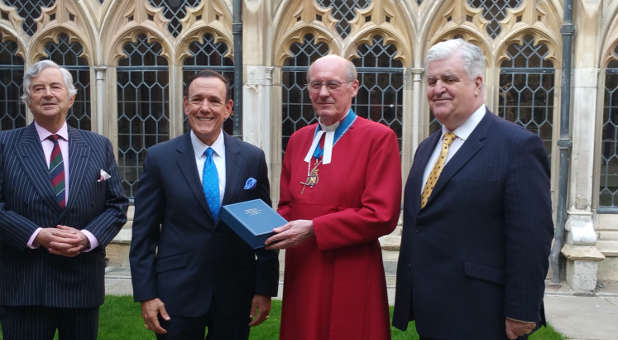 The Dean of Windsor David Connor accepts the special Bible for Queen Elizabeth II from Charisma Media CEO Steve Strang, left, at Windsor Castle in England on May 8.