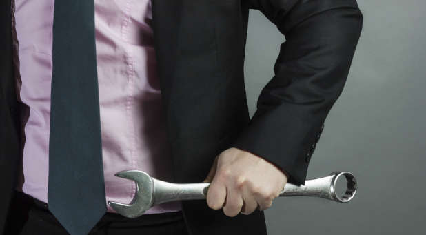 Businessman carrying wrench
